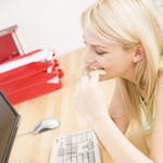 Woman eating crisps at desk - Healthy snacks to keep at work, by Adrienne Wyper