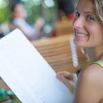 Woman reading restaurant menu - How to make healthier choices at chain restaurants, by Adrienne Wyper